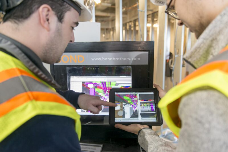 Two men in safety equipment in front of a BIM Box and holding and pointing at an iPad with Building Information Modeling/3D drawings on it.