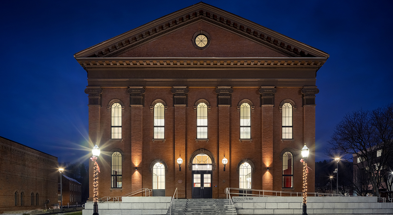 Front facade at night of Fitchburg City Hall in the winter. Two street poles in front of the building have winter lights strung on them.
