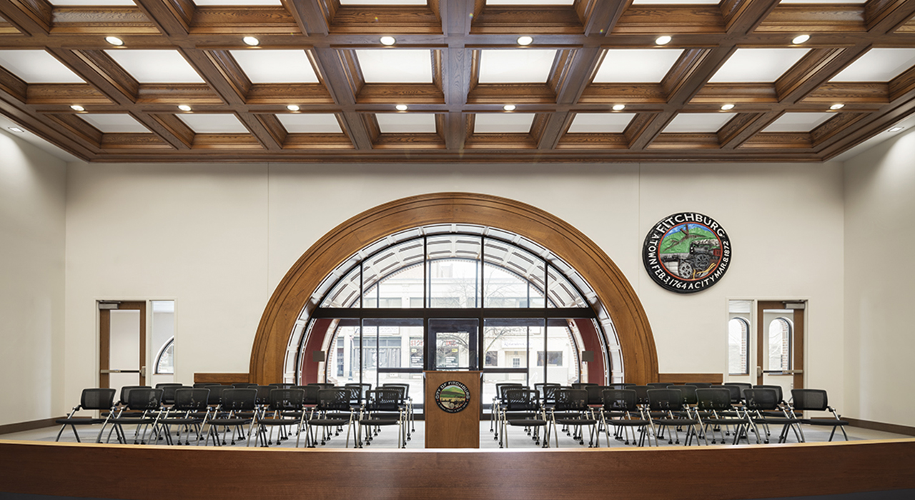 Fitchburg City Hall council chambers in Legislative Building. Chairs for the public are arranged in front of the arched doorway. There are coffered ceilings. The building was a former bank donated by Bank of America.