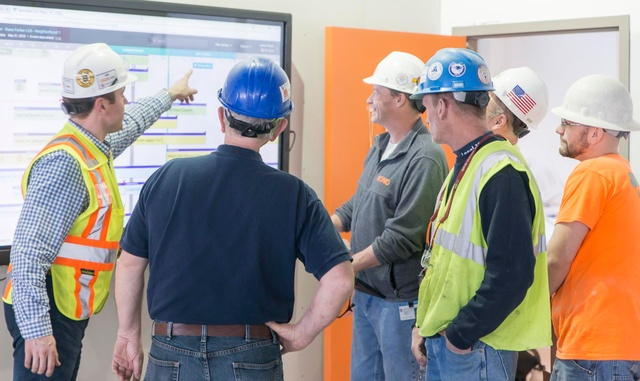 BOND staff with subcontractors in front of a large flat screen TV looking at a schedule together for a pull planning session.