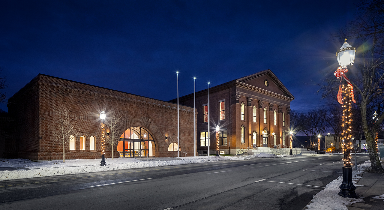 Exterior of Fitchburg City Hall at night in the winter. Building complex is shot at an angle and shows historic building and former bank at left renovated into Legislative Chambers.