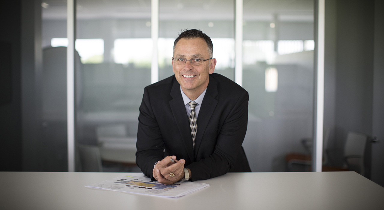 Man with suit and tie leaning on a counter in an office with conference room behind him
