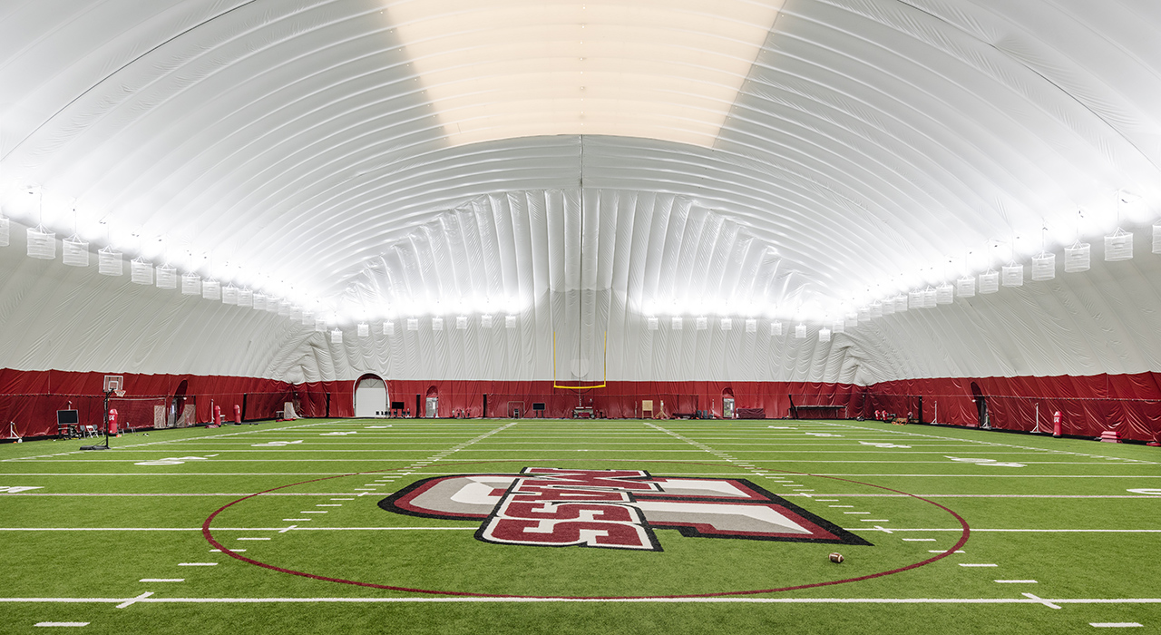 Interior of a Seasonal Air Supported Athletic Facility. Logo of UMass Amherst in foreground. White inflatable structure over field.