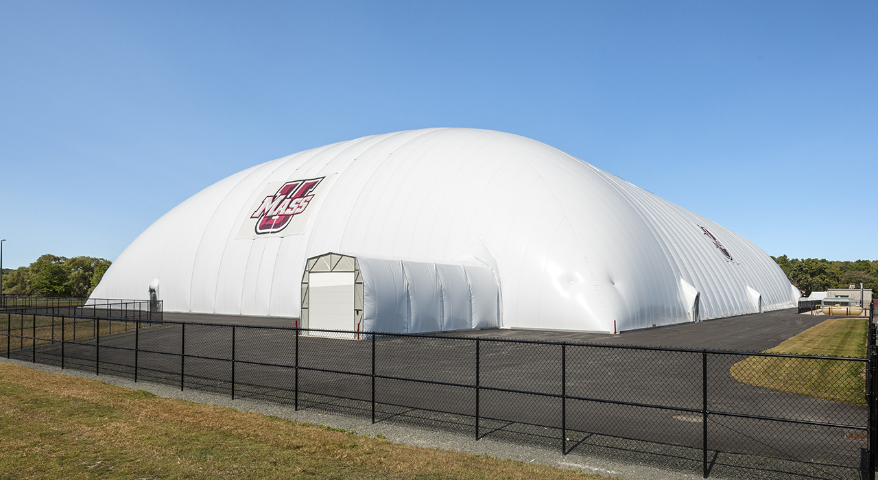 Exterior of a Seasonal Air Supported Athletic Facility. Logo of UMass Amherst on the inflatable structure. Pavement and fencing around perimeter.