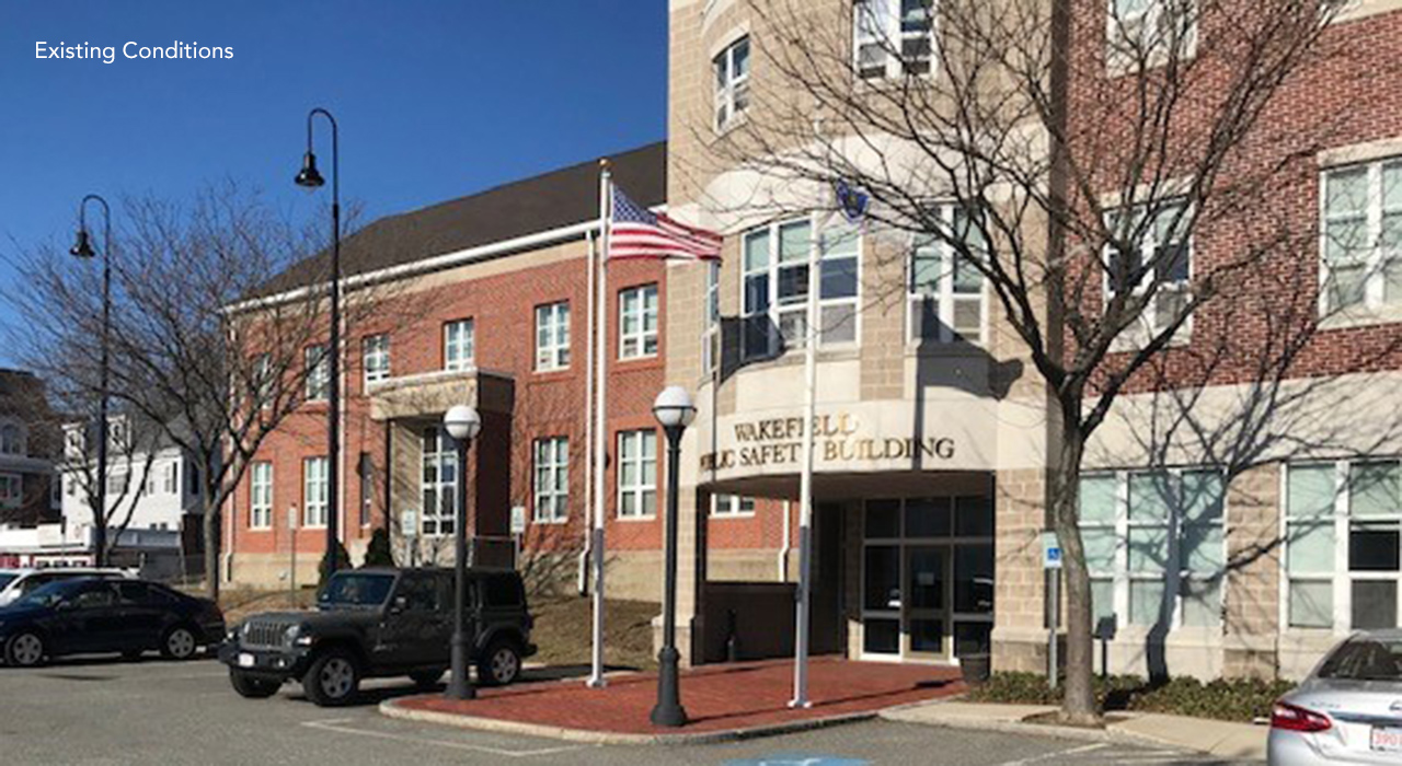 Front of Wakefield Public Safety Building. USA and State flag poles in front of brick and masonry facade. Existing conditions.