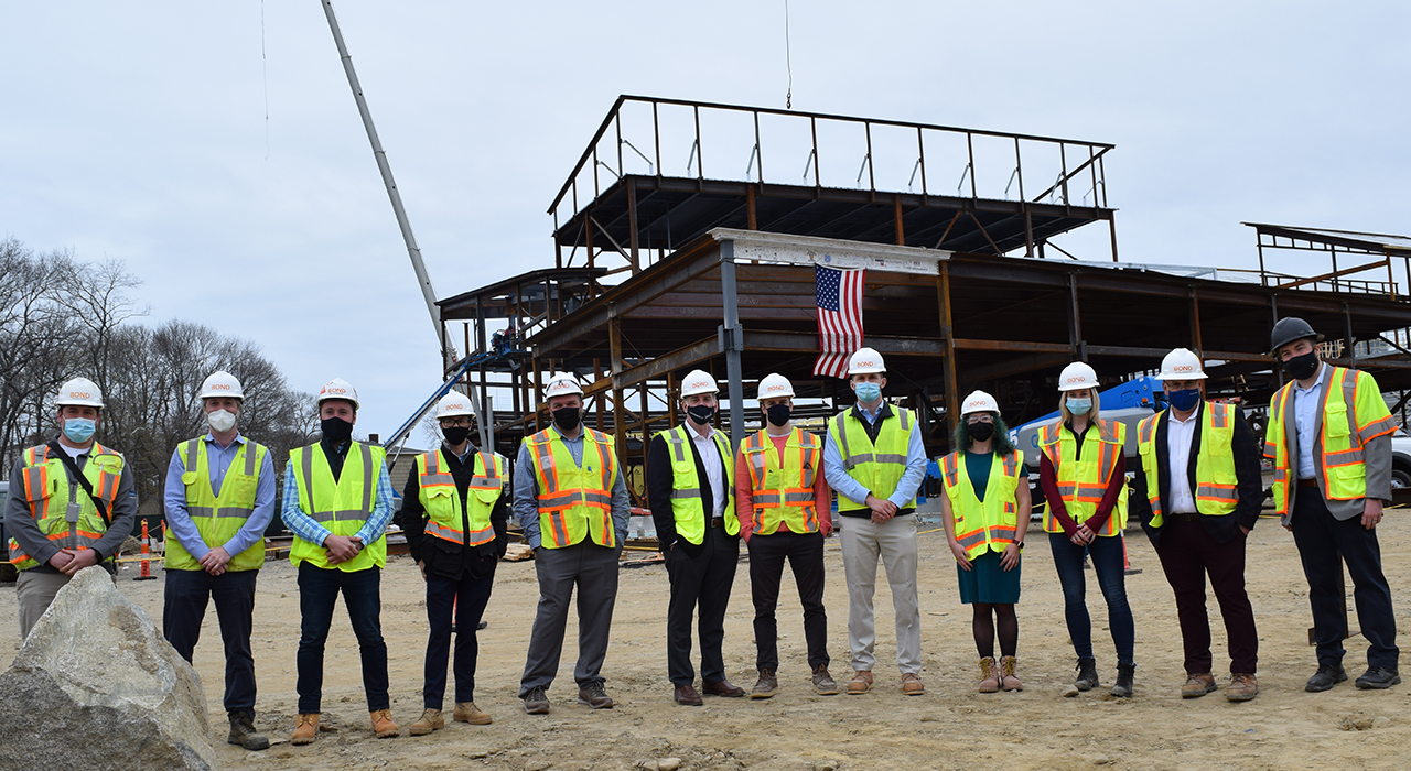 Town of Weymouth MA Maria Weston Chapman Middle School Topping Off - project team in hardhats, masks, and vests assembled in a line in front of a steel structure with the newly placed signed beam and an American flag