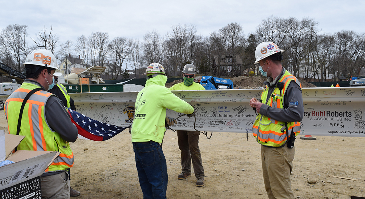 Weymouth Maria Chapman West Middle School Topping Off. Four construction workers with steal beam signed by townspeople and with logos of the firms involved.