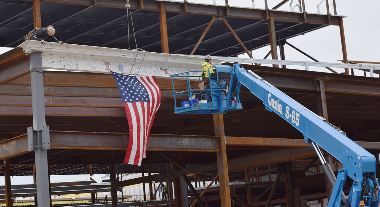Town of Weymouth MA Maria Weston Chapman Middle School Topping Off - workers place topping off signed steel beam draped with an American flag. Blue crane in foreground.