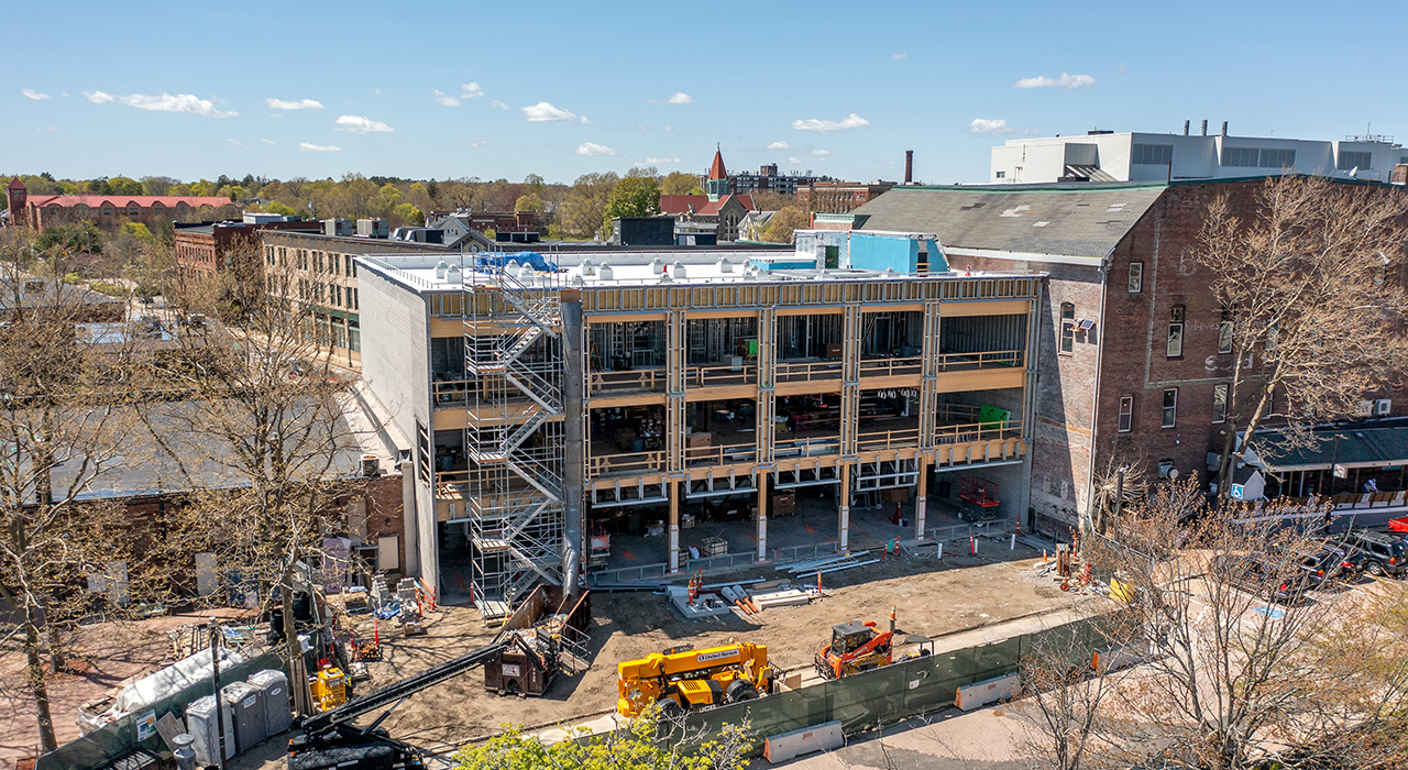 Photograph from a drone by Will Horne of the new Massachusetts Department of Unemployment Assistance building under construction in downtown Brockton. Shown are constructed masonry walls on the sides with Cross Laminated Timber (CLT) slabs. An orange cherry picker is in front of the partially constructed building.. Photo by Will Horne.