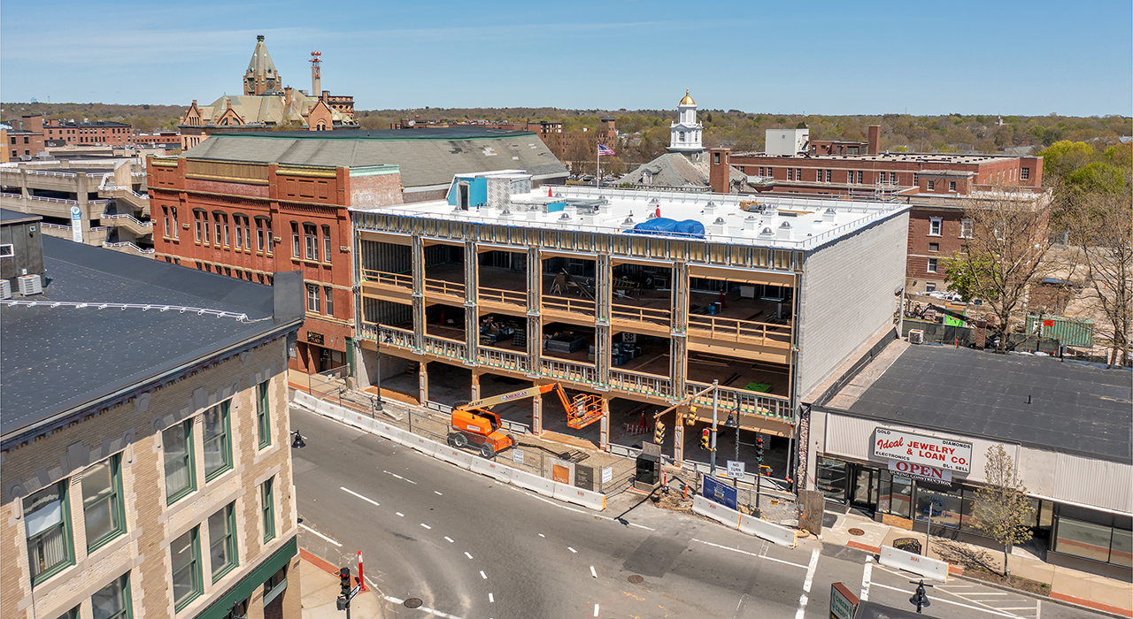 Photograph from a drone by Will Horne of the new Massachusetts Department of Unemployment Assistance building under construction in downtown Brockton. Shown are constructed masonry walls on the sides with Cross Laminated Timber (CLT) slabs. An orange cherry picker is in front of the partially constructed building.